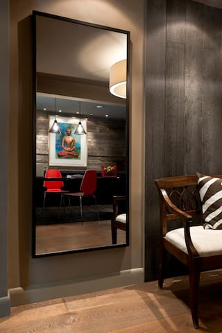 Full length mirror reflecting desk and reclaimed wood wall.
