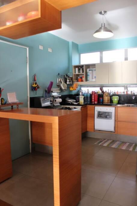 Nossa querida cozinha, prática e iluminada. Micro ondas, máquina de lavar prato, fogão e geladeira.