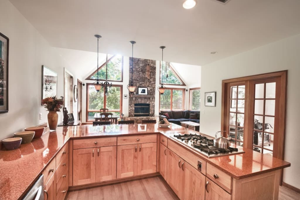 The gourmet kitchen is the hub of this home. Decks are through the french doors to the right. The great room with stone fireplace is in the background.