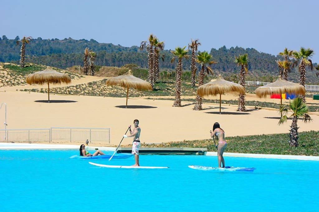Playa artificial, con salvavidas y actividades guiadas para niños y adultos.