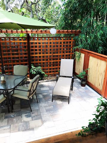 Patio equipped with lounge chair, umbrella, dining set, trellis and bamboo accents