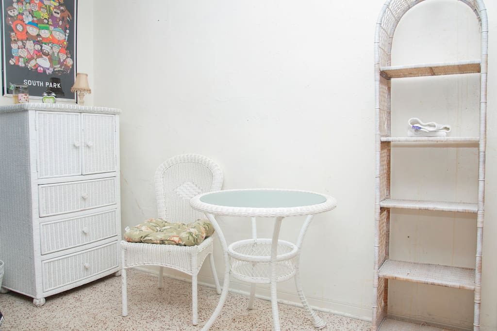 Dresser in bedroom with chair and shelving