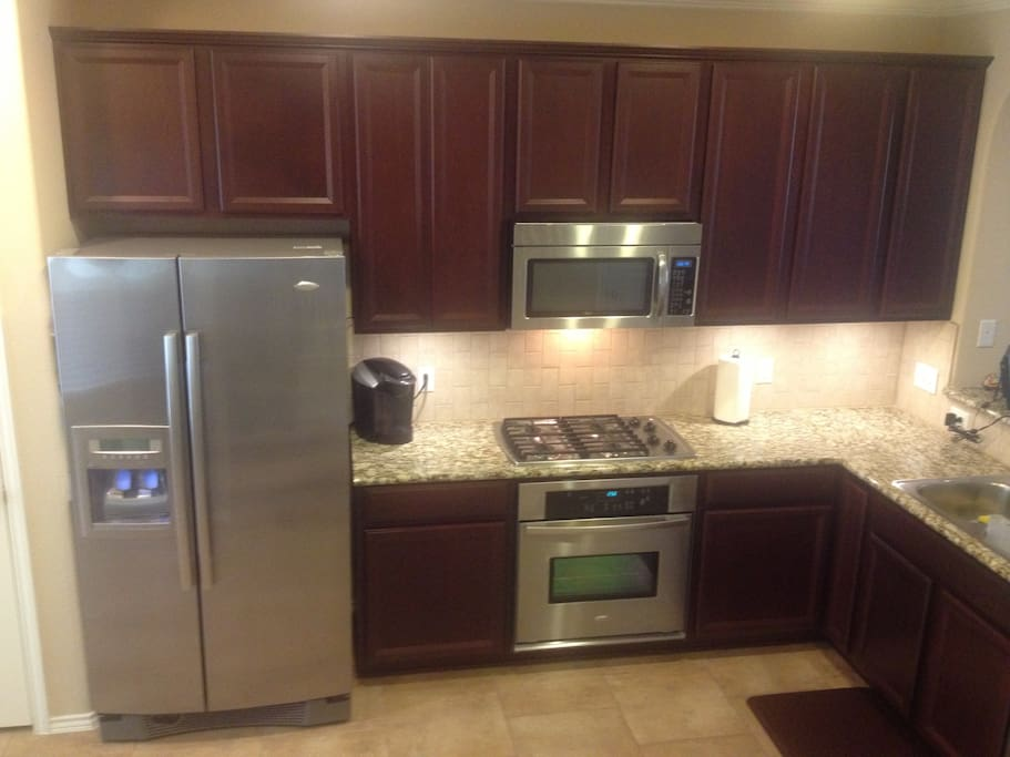 Kitchen with modern appliances and granite counters.