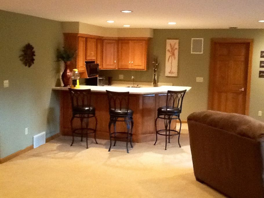 Wet bar with microwave, mini refrigerator, coffee pot, toaster, & dishes. (note no stove)