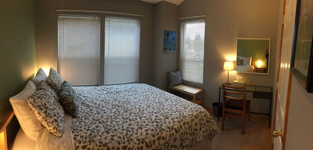 One of two bedrooms with a queen bed and small workspace
