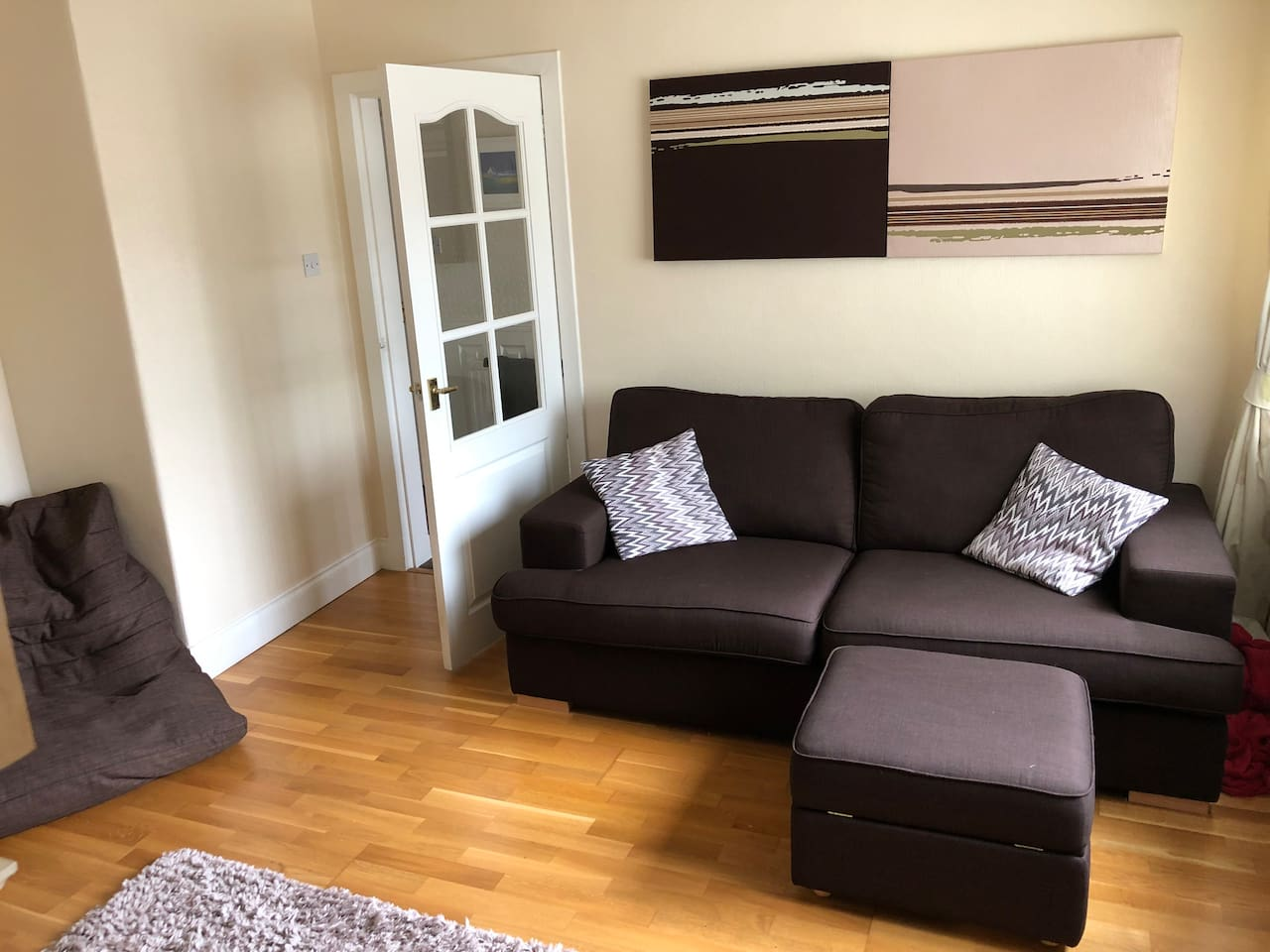 Private access living room includes very comfy 2 seater sofa and footstool as well as bean bag seat.