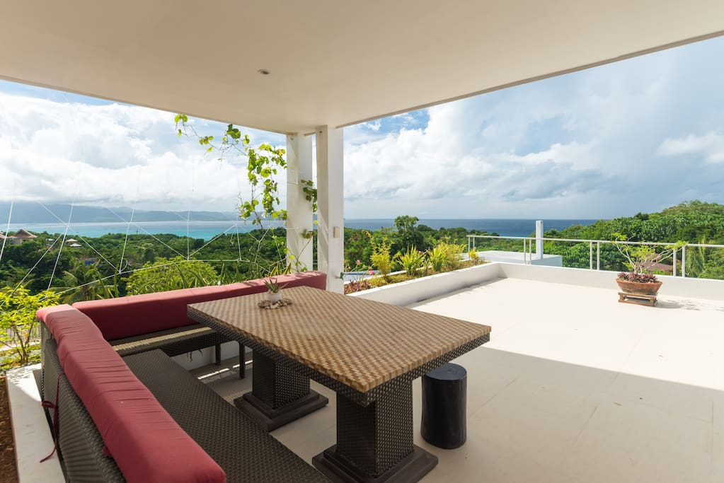 Southwest sea view from private terrace with dining area and garden.  Witness Flying Foxes flying to Panay 20-40 minutes after the sun sets.