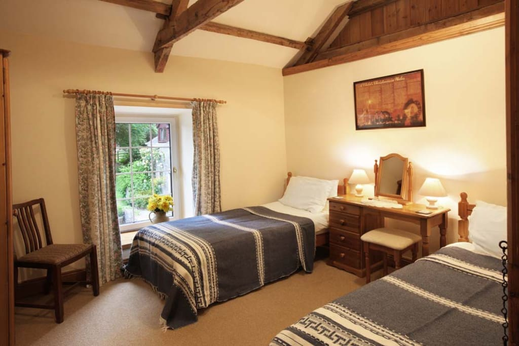 The Twin Bedroom overlooks the courtyard, lawns and sheep grazed paddock.