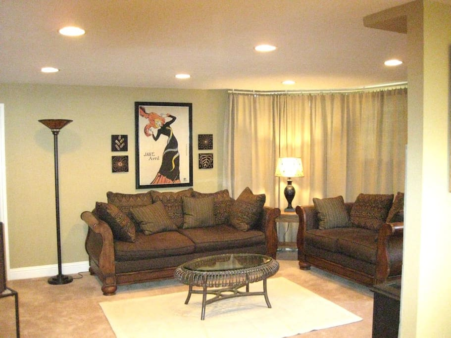 Comfy couches and floor to ceiling drapes for privacy