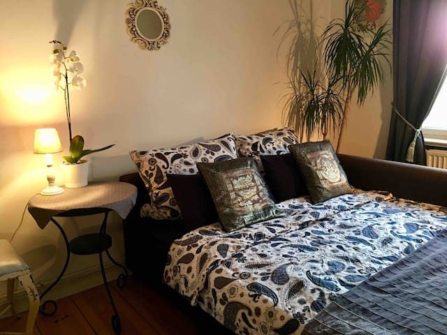 """Your comfortable bed sofa (140 x 200) in my typical Berlin """"Altbau"""" flat (built 1890). Towels, shampoo, shower gel, and more will be provided for you."""