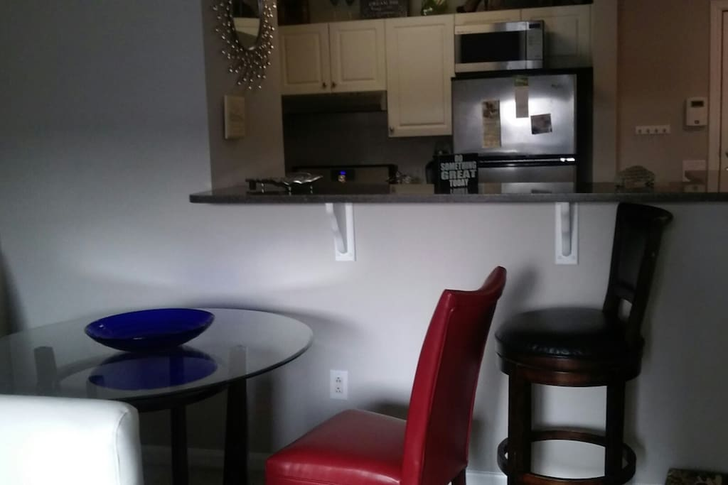 glass table for two with red leather chairs ...one chair for island..looking into kitchen