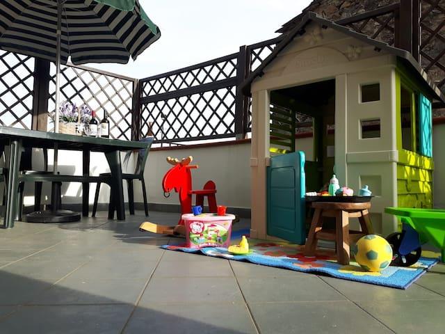 Cortile della casa con zona per mangiare all' aperto e spazio gioco per bimbi