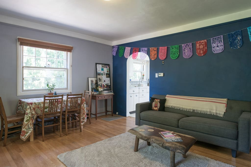 Bright living room/dining room with a table for up to six, large couch, big windows, and an iMac that serves as the TV.