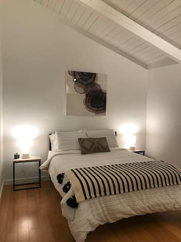 Back bedroom with queen size bed, vaulted ceiling and window with view into the forest
