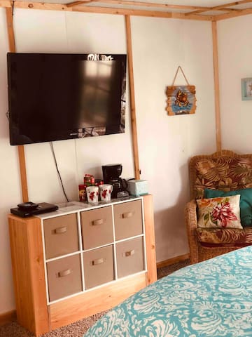 The room has a TV with DVD player and local channels, plus a TON of movies in the drawers for you to peruse! A coffee maker and mugs, as well as water and light refreshments, are available on the storage unit.