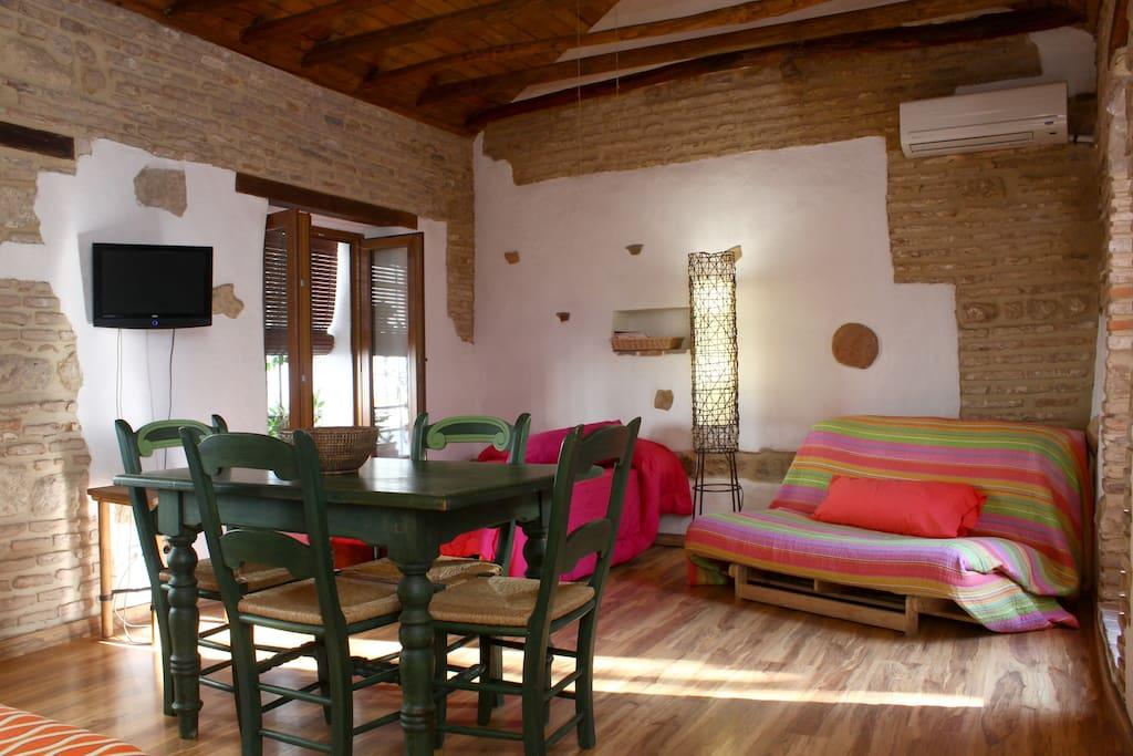 Dormitorio-comedor con cama de matrimonio de 1.50, sofá-cama de 1.20 y cama supletoria de 1.00 mts con acceso a terraza.