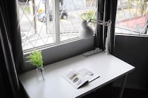 Spacious Workdesk By The Window with Power Plugs and Desk Lamp