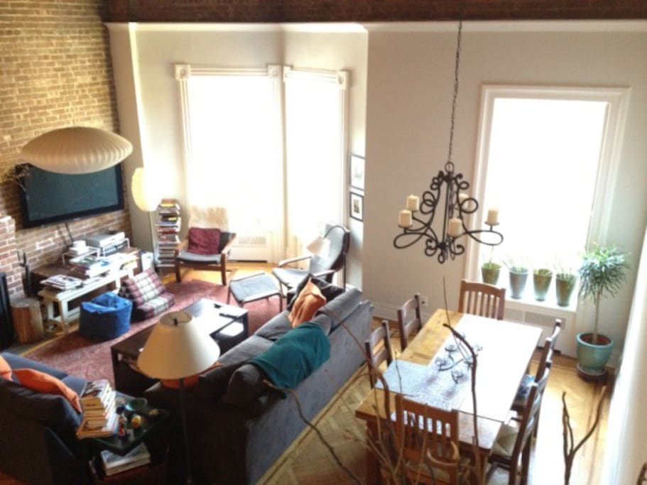 Open living room (on left) and dining room (on right) with lots of light and 17 foot ceilings.