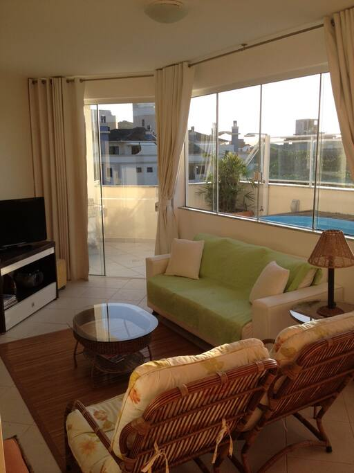 Sala de estar com o terraço da piscina ao fundo.
