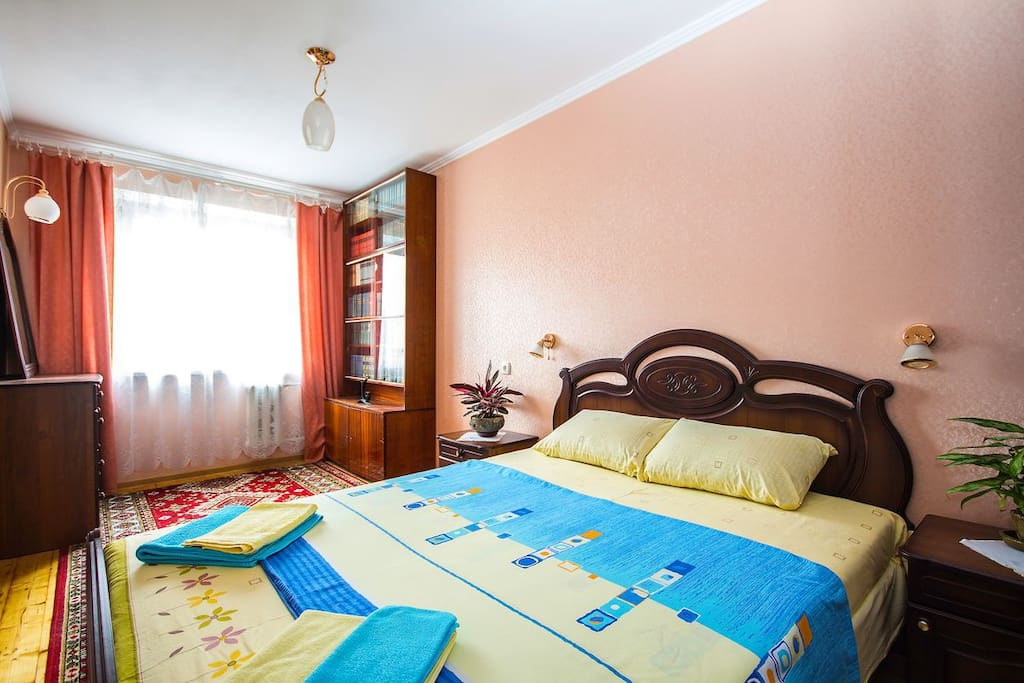 Clean bedroom with queen-size bed and flat tv. On the other side of the bedroom there is a big window to the quite green garden, bookshelf with classical russian literature and big mirror.