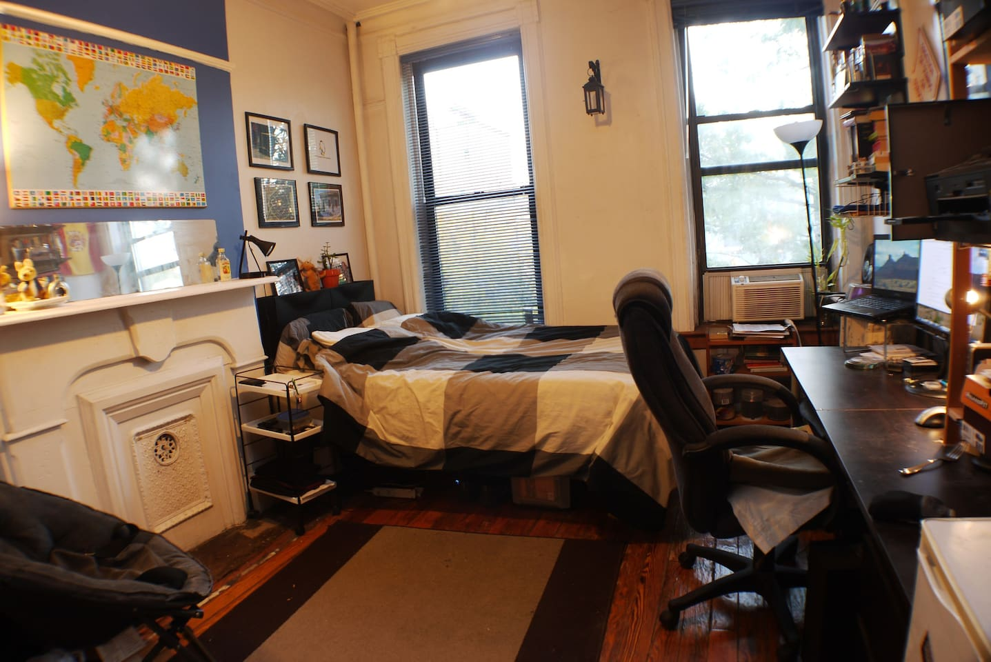 Large bedroom with double bed, ornamental fireplace, desk, TV/monitor, and personal fridge
