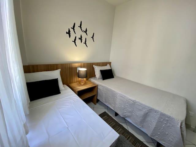 Quarto de solteiro 3: com 2 camas de solteiro + 1 cama auxiliar e estante aberta.