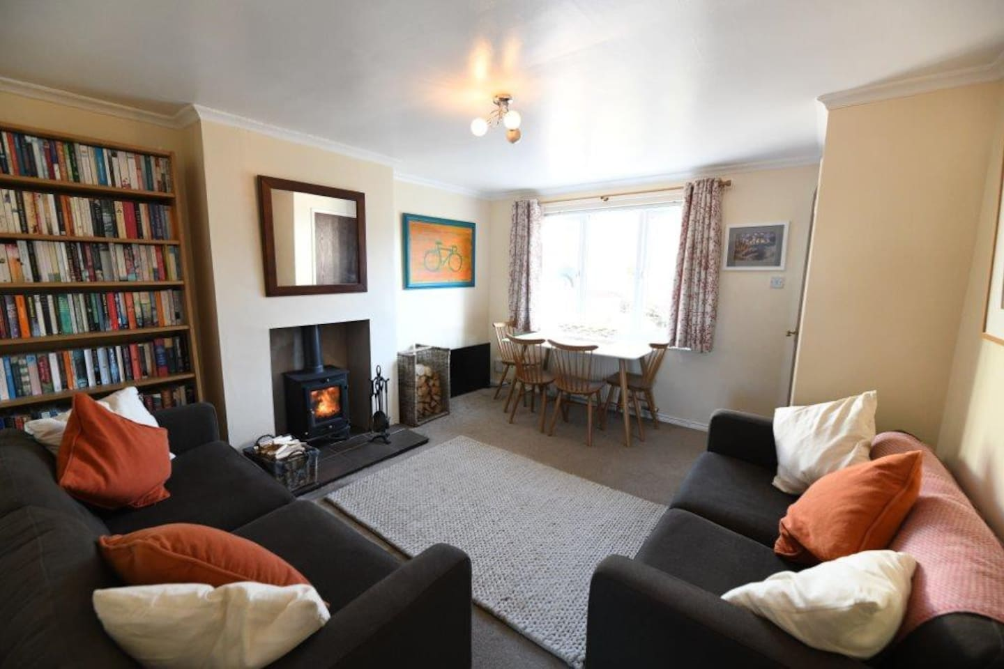 The shared living / dining room, with toasty logburner, smart TV, and lots of books to dip into.