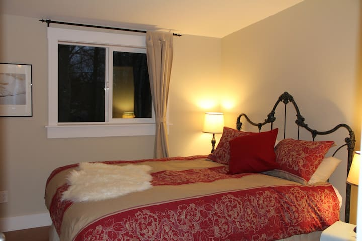 Cozy bedroom with queen size bed and access to private garden patio.
