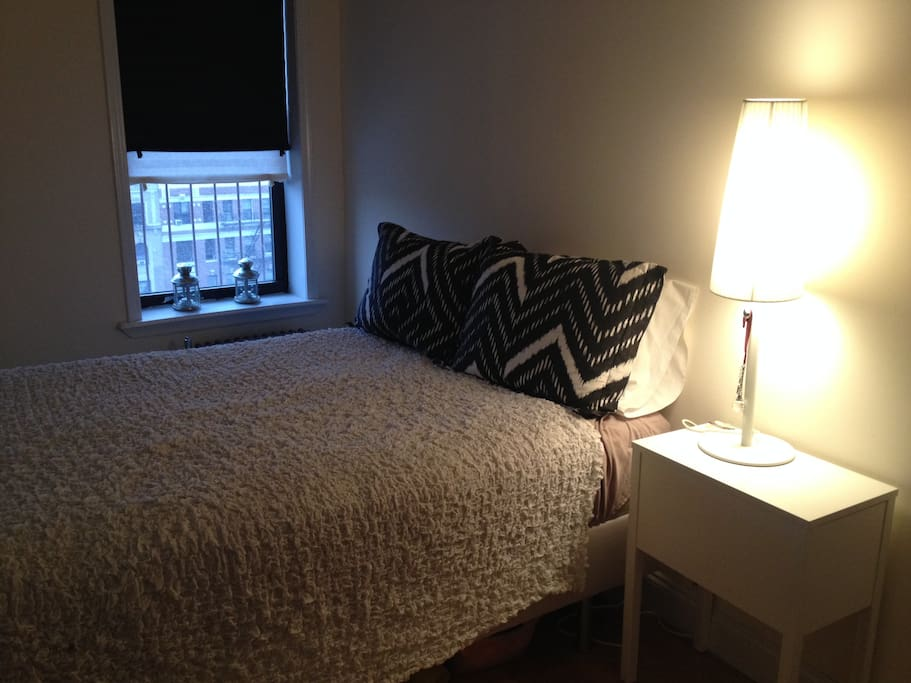 Cozy bedroom with double-sized bed and bedside table/lamp - lots of natural light