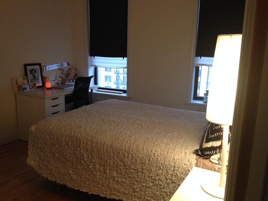 Cozy bedroom with double-sized bed, bedside table/lamp, and desk/chair.