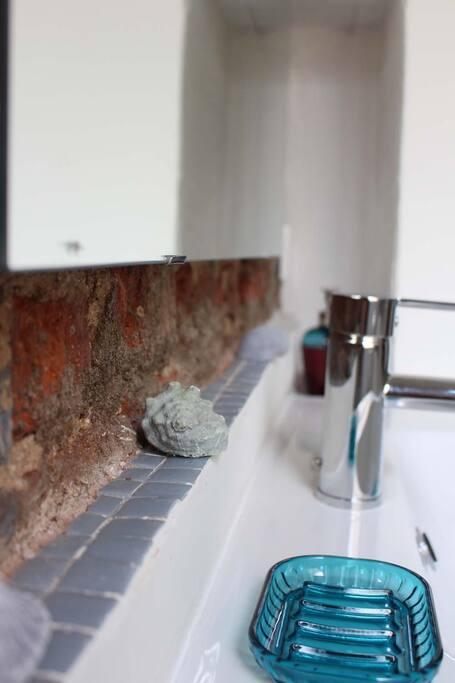 Moderno baño con gresite y pared de ladrillo visto.