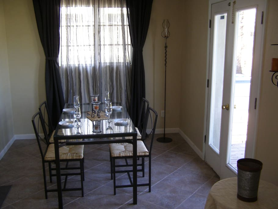 Dining room with tile floor and glass top table. Glasses, plates silverware included