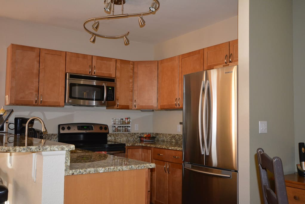Modern fully stocked & equipped kitchen w/granite countertop & stainless steel appliances & plenty of cooking gear!