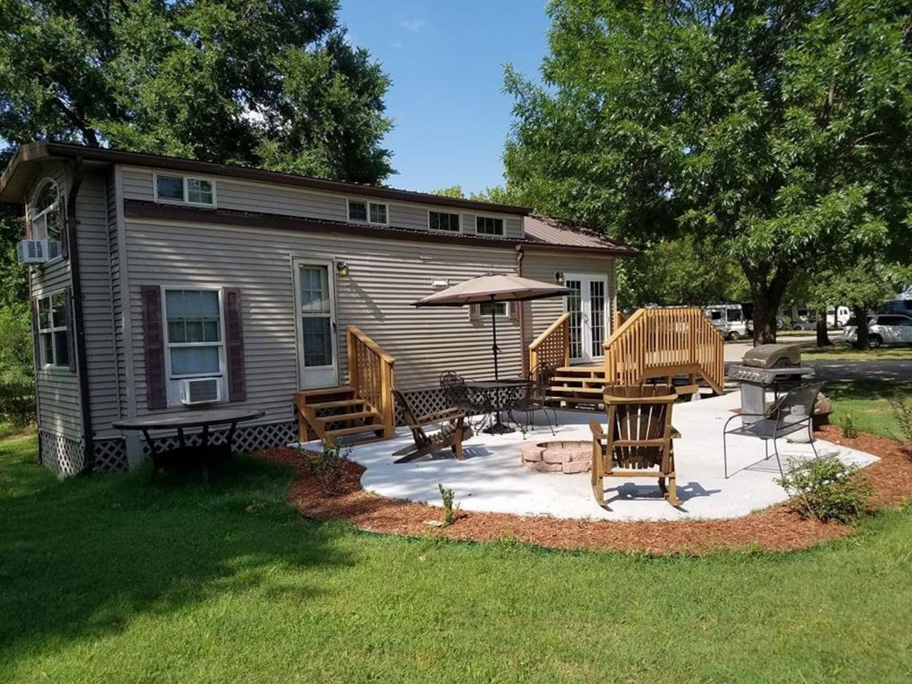 Beautiful outdoor space with gas grill, seating, stone fire pit, adirondack chairs and more.