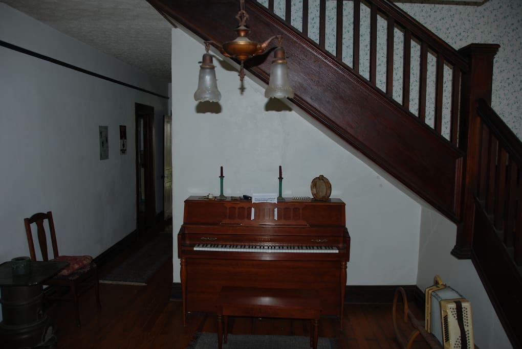 Foyer with piano and pool table adjacent.