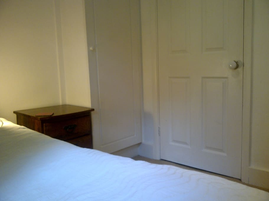 View from window single room with slim line wardrobe, chest of drawers, bed side table and lamp.
