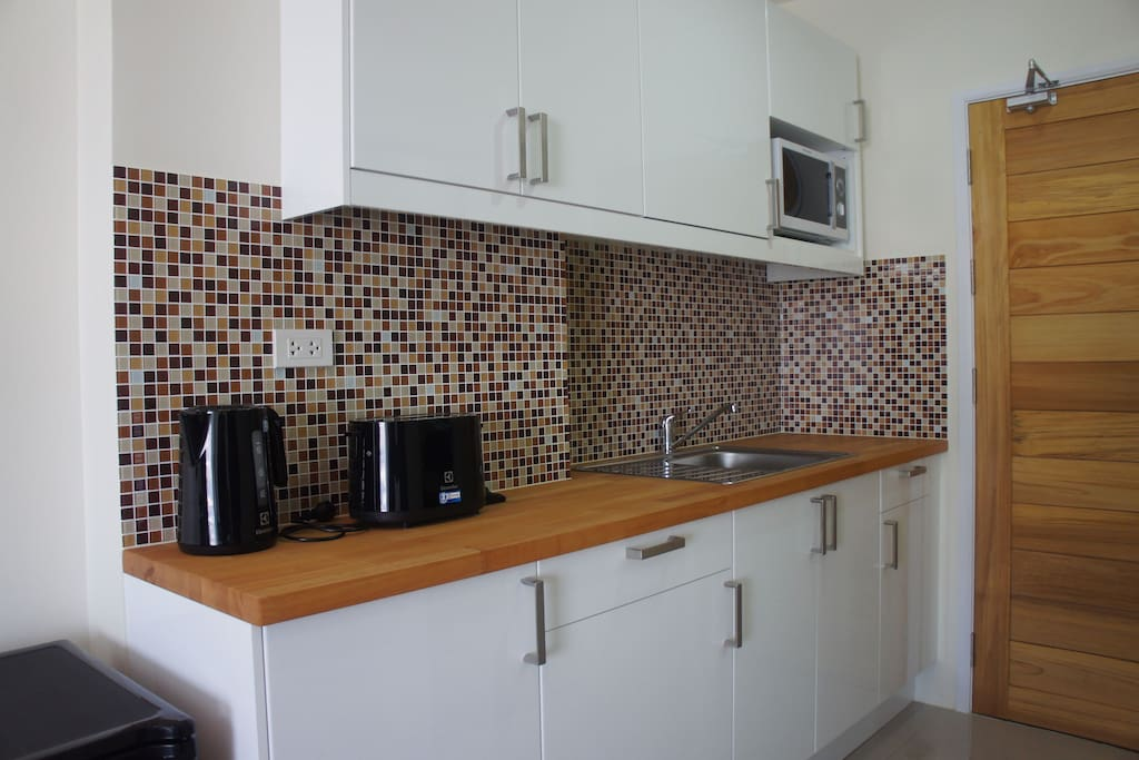 Ikea fitted kitchen with sink, microwave, toaster, kettle and refrigerator.