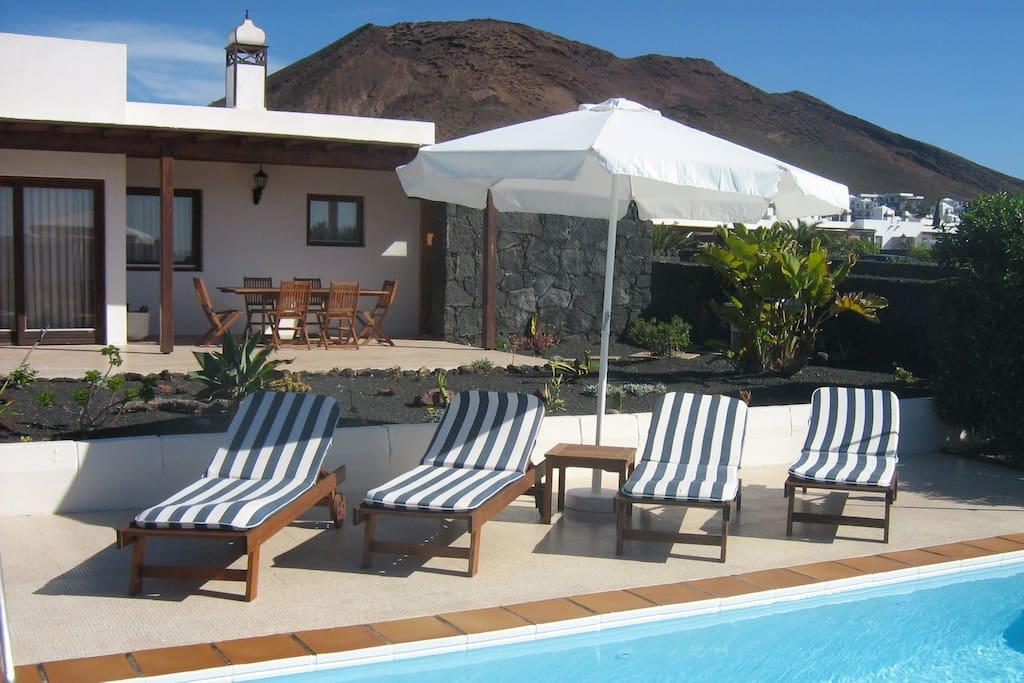 Piscina climatizada con tumbonas y terraza