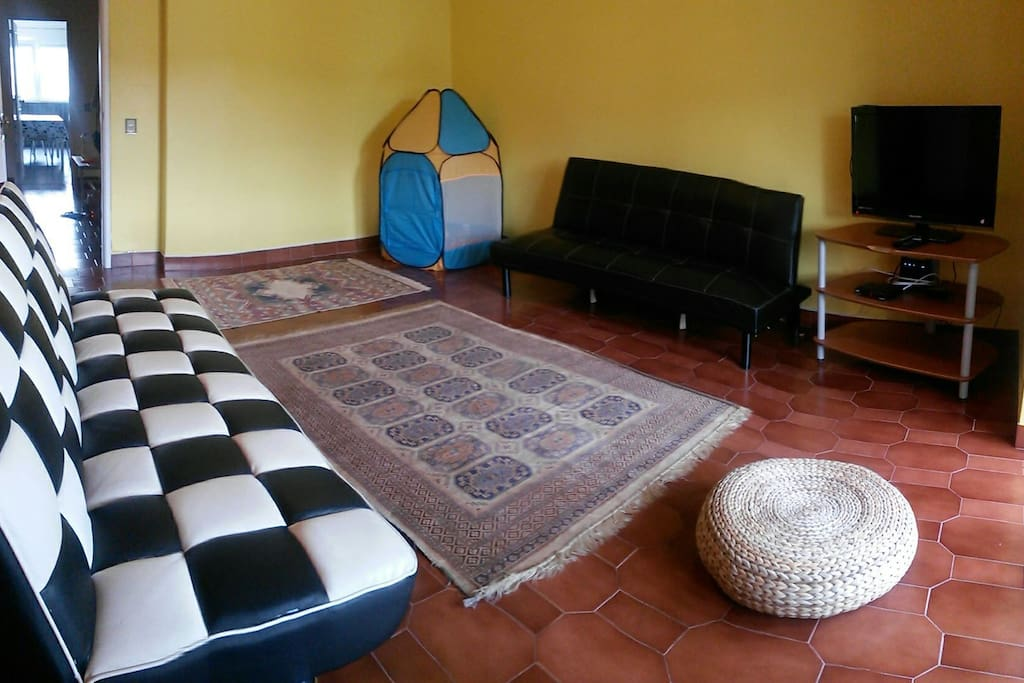 Sala com LCD, TV cabo e mini parque para crianças.