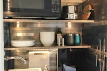 Kitchenette with sink, hot plate, microwave and coffee maker. Fully equipped with plates, bowls, cups, glasses, silverware, pots and pans