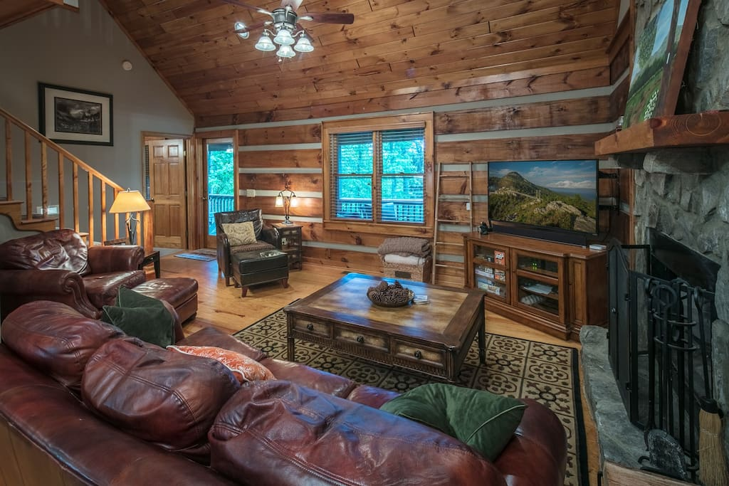 This comfortable couch and  log decor is cozy and warm.