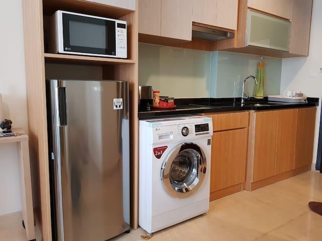 Kitchenette with electric stove, microwave, fridge and washing machine