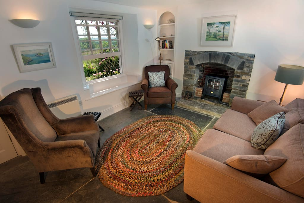 The slate-floored living room overlooks the west field and the garden. There's a woodburner-style stove in the fireplace