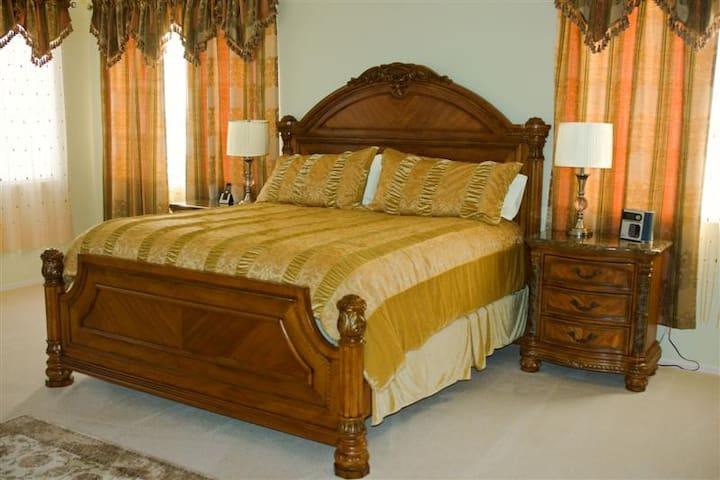 King size masterbedroom with high-end furniture and marble tops. Attached large walk-in closet.