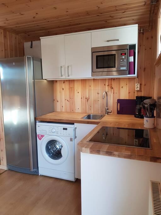 Köket, utrustat med spis, ugn, mikro, kyl och tvättmaskin.