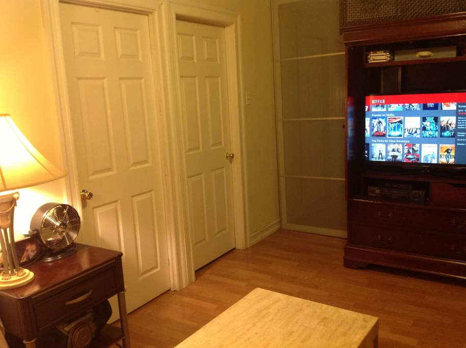 Large Living room with TV and Media/Bluray player. Sliding glass door leads into corridor toward apartment entry.