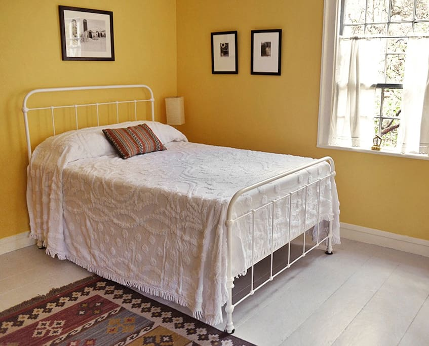 The double bed features a vintage iron bed frame which adds to the character of the space.