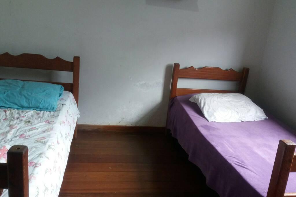 Quarto duplo ventilado, com duas cama de solteiro, escrivaninha e capacidade máxima de 4 pessoas (1 beliche e 2 chão)