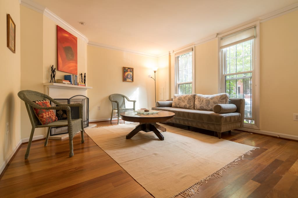 Spacious, sunny living room (couch converts to comfortable queen bed).   Teak hardwood floors, wood-burning fireplace.