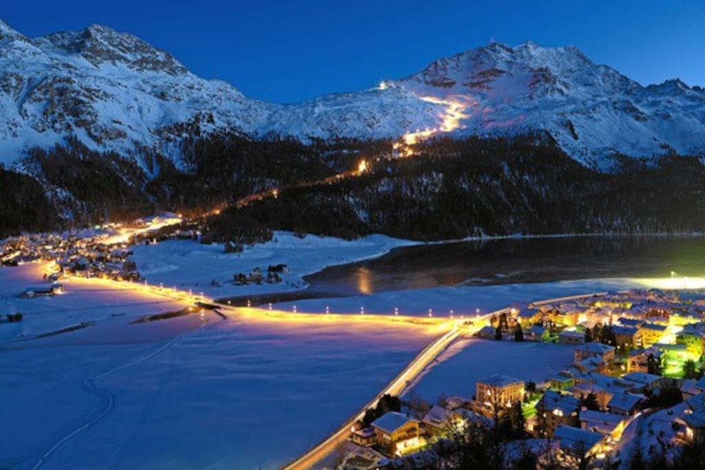 Vista invernale con Piz. Corvatsch illuminato per discesa notturna